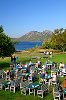 Outdoor seating at the Jordan Pond House Restaurant with the North and South Bubbles in the distance
